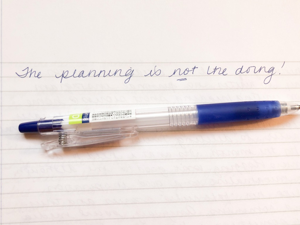 """A notebook with a pen. The words above the pen say """"The planning is not the doing."""""""