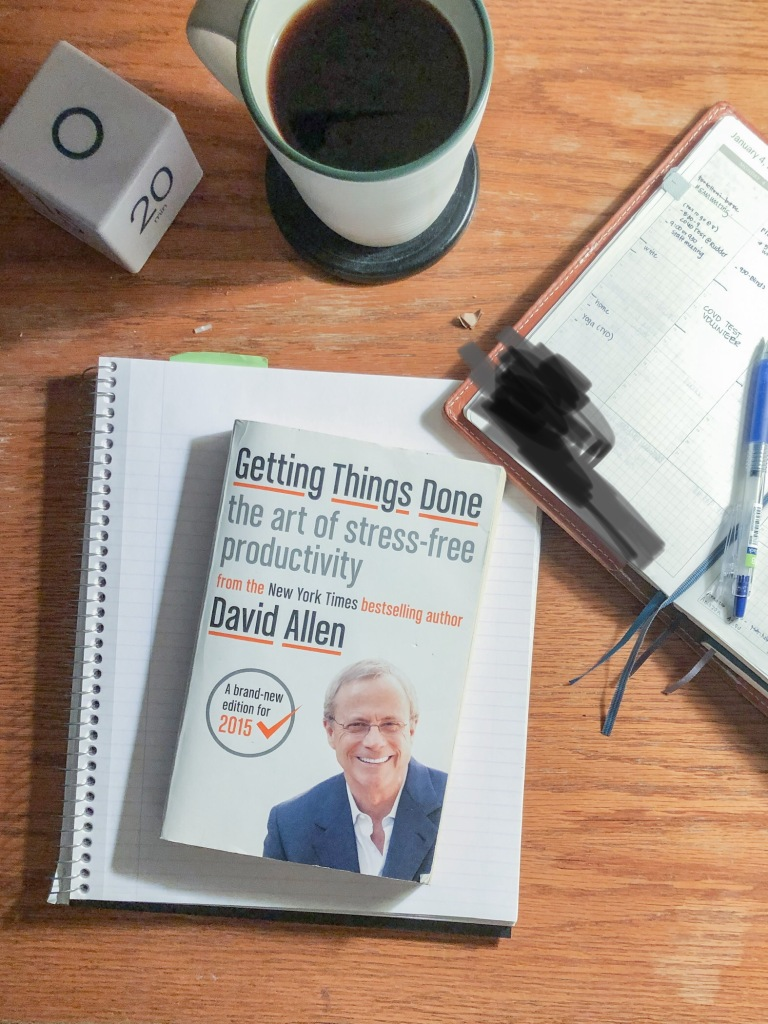 A desktop with a note book, a planner, a cup of coffee and a copy of David Allen's book Getting Things Done