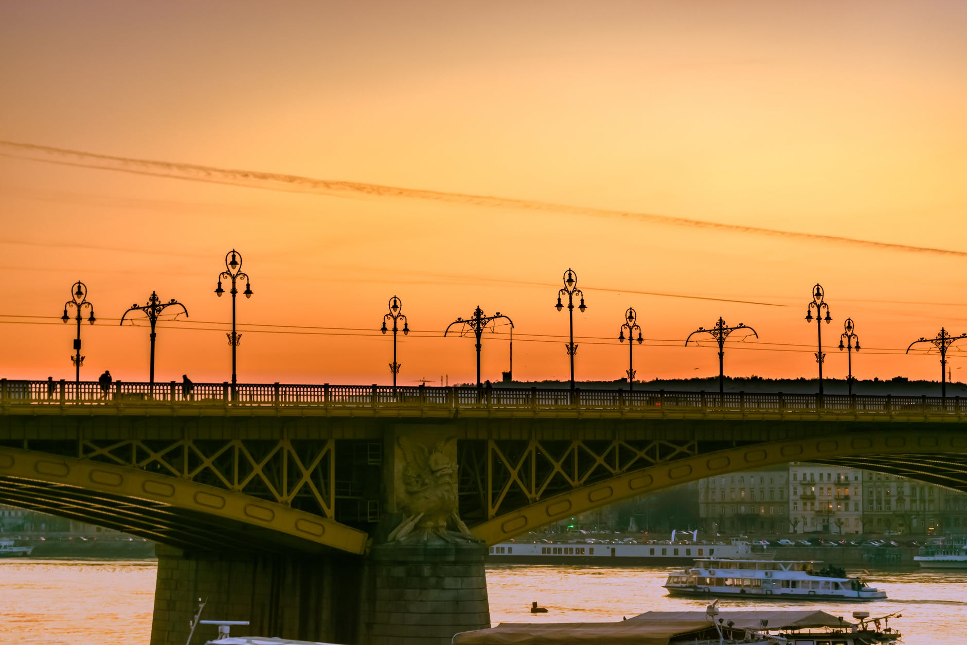 A photo of a bridge over a river at sunset, with tour boats passing under.