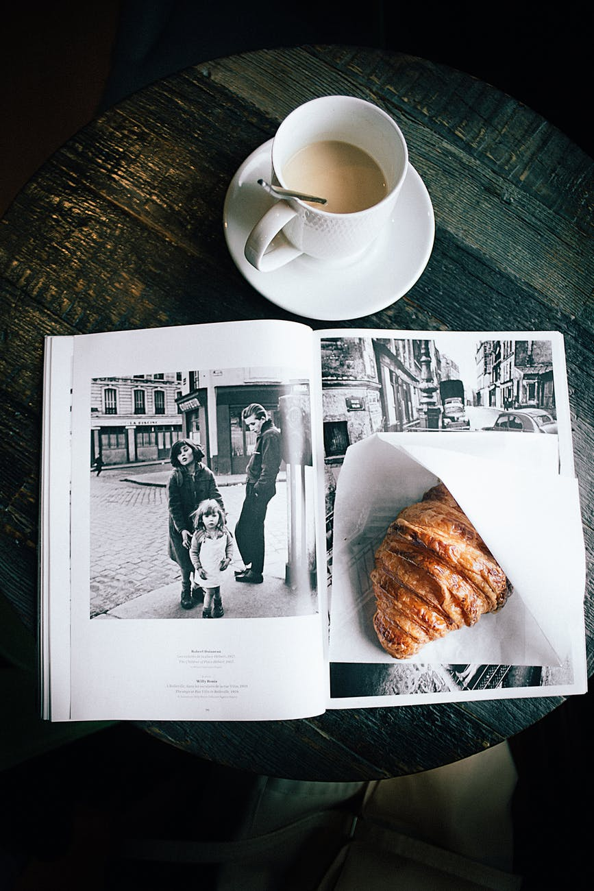 A photo book with a croissant and a cup of coffee.