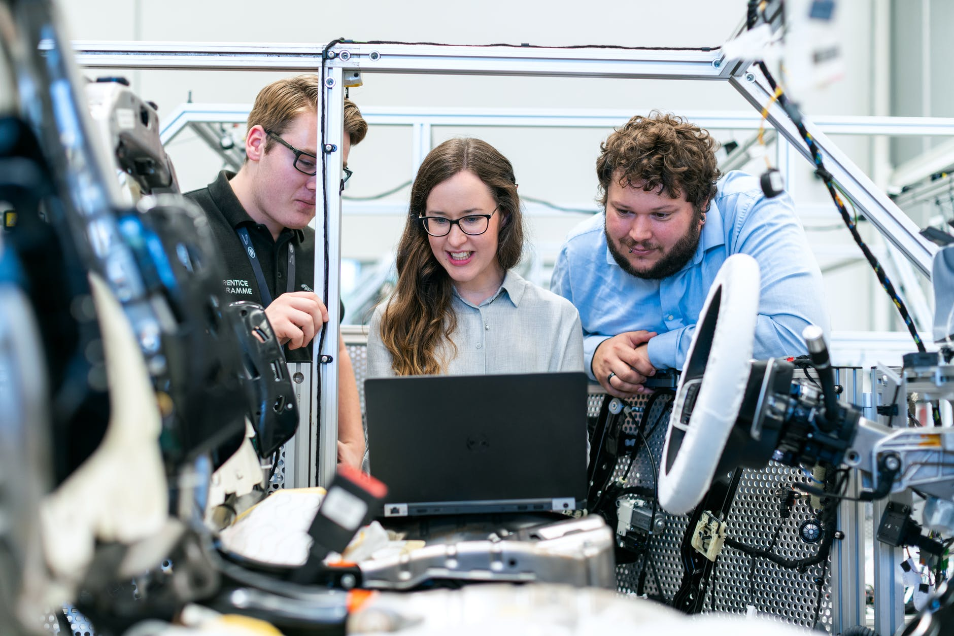 three engineers in a factory are looking at a laptop in an automobile frame