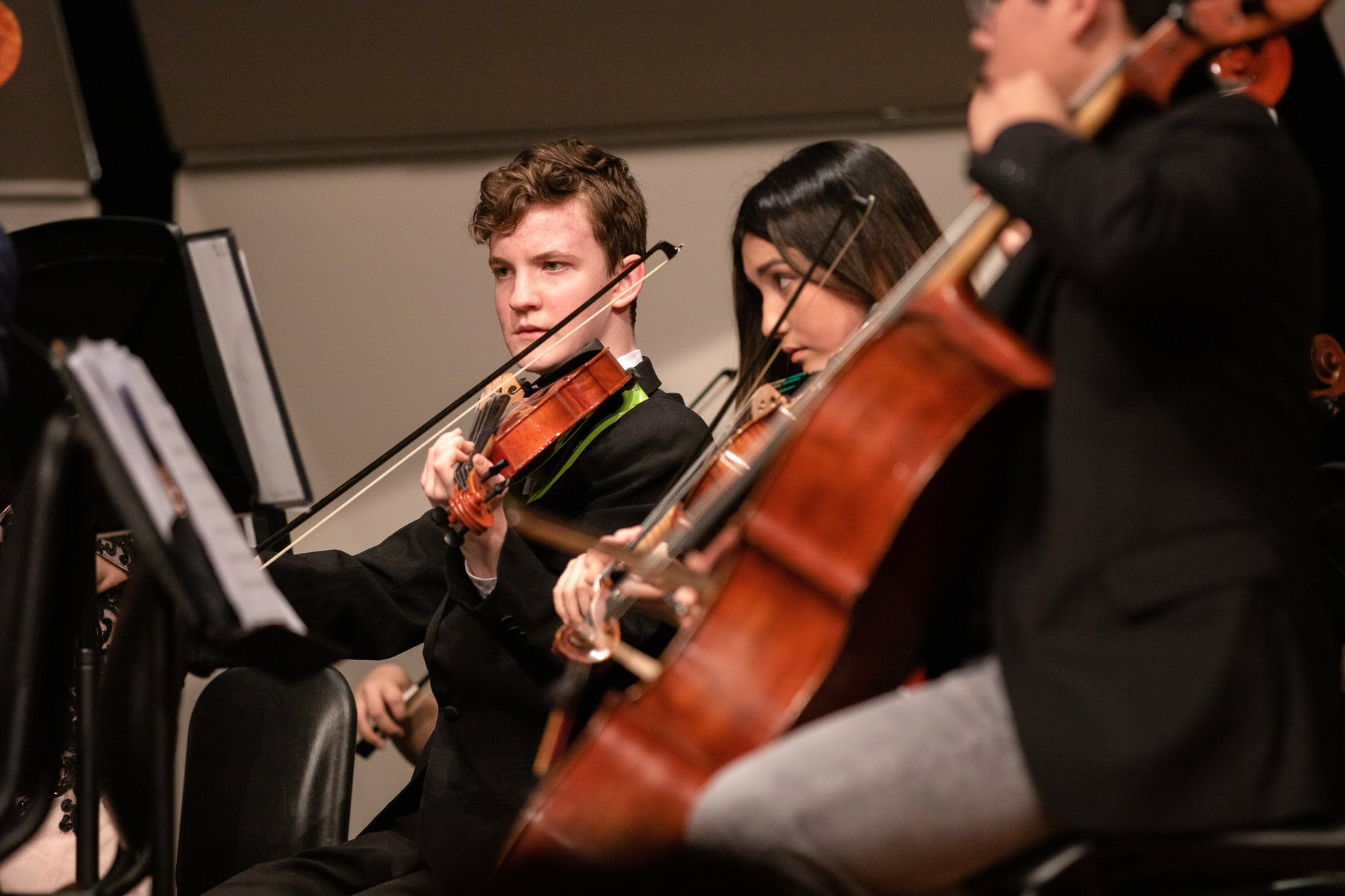 two violin players and a cello player looking at music while they perform