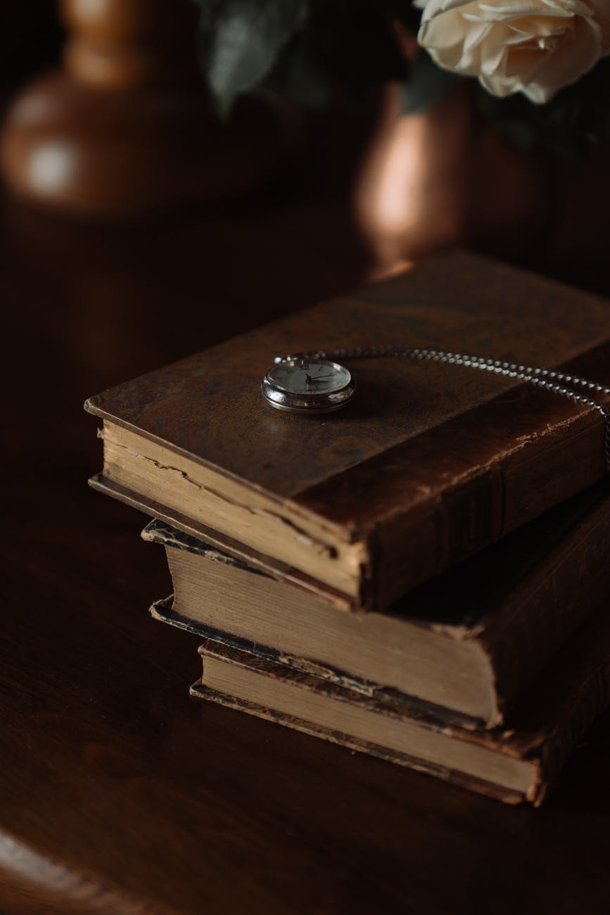 A pile of old leather bound books with an open pocket watch on top