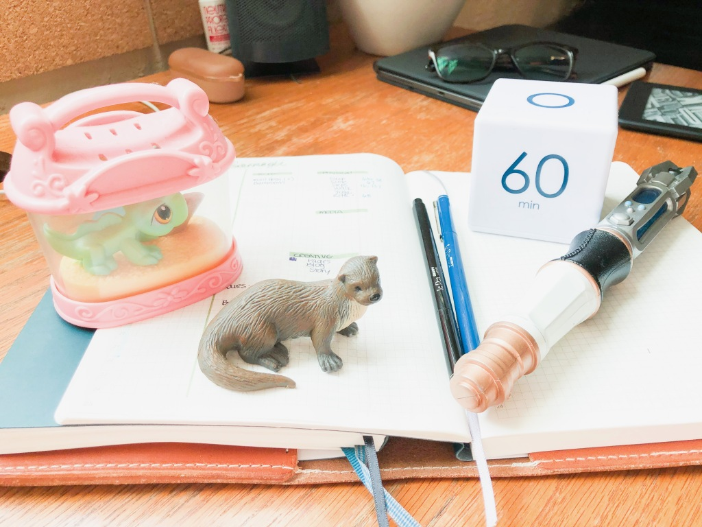 An open planner with two pens, a toy iguana, a toy otter, a timer and a replica of Dr. Who's sonic screwdriver