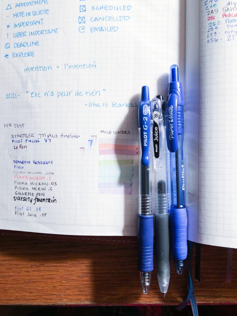 A photo of a planner with three pens side by side.