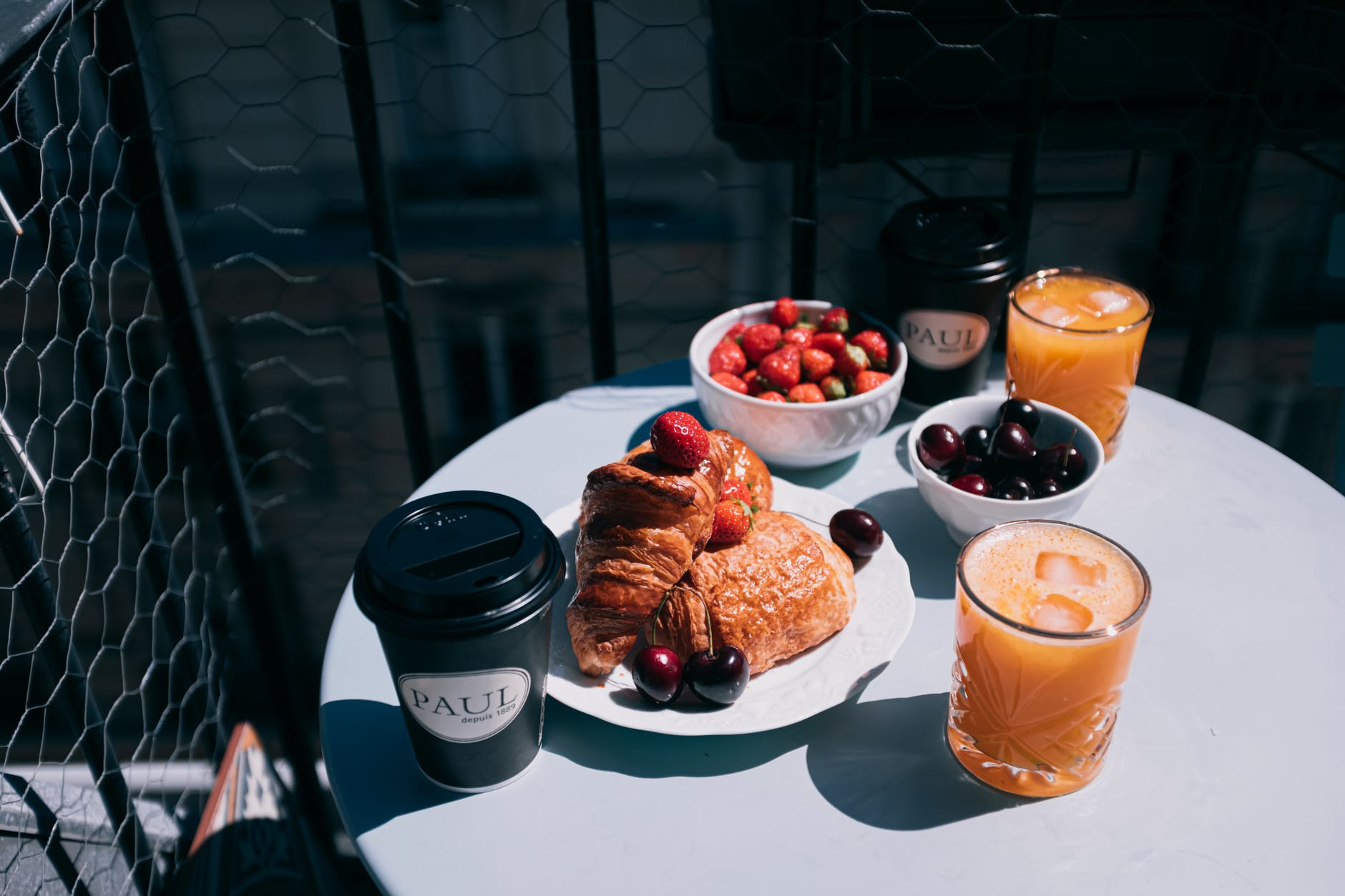 A small round table with croissants, fruits and coffee.